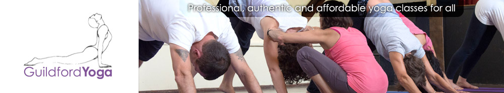 A group of GuildfordYoga students performing downward dog pose with Luci Phipps adjusting one of the participants