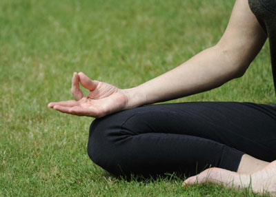 A girl sitting in a yoga pose demonstrating a yoga hand gesture.